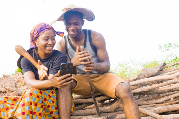 excited african couple doing internet banking on their farmland. male and female farmers using smartphone