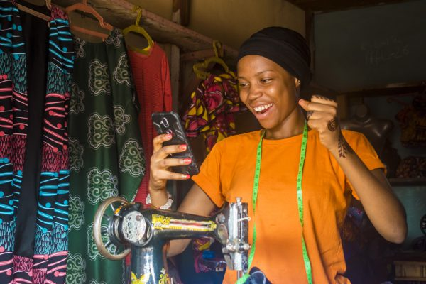 young african woman who is a tailor feeling excited and happy and jubilant while viewing content on her mobile phone