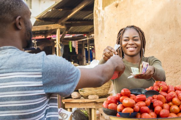 black girl selling tomatoes in a local african market to a male customer smiling and feeling happy and satisfied