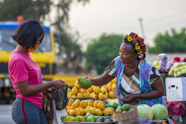 A young African buying fruits from the market and wearing face mask for protection - Receiving a purchased item from a local happy food vendor